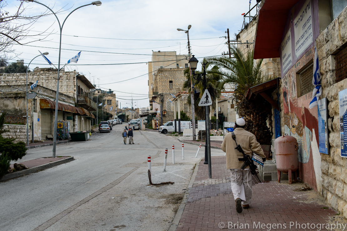 Settlers walking the streets with M-16 weapons in the city centre of Hebron.